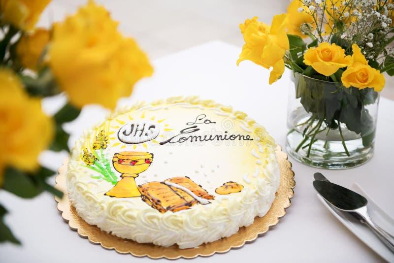 Erstes Konzept der heiligen Kommunion, schöner Kuchen mit Text auf italienisch: erste heilige Kommunion und gelbe Rosen auf einer stockbilder