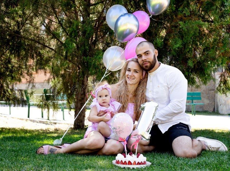 Erstes Lebensjahr Geburtstag glückliche Eltern Familienfoto Kuchen eine Partei Urlaubskonzept lizenzfreies stockbild