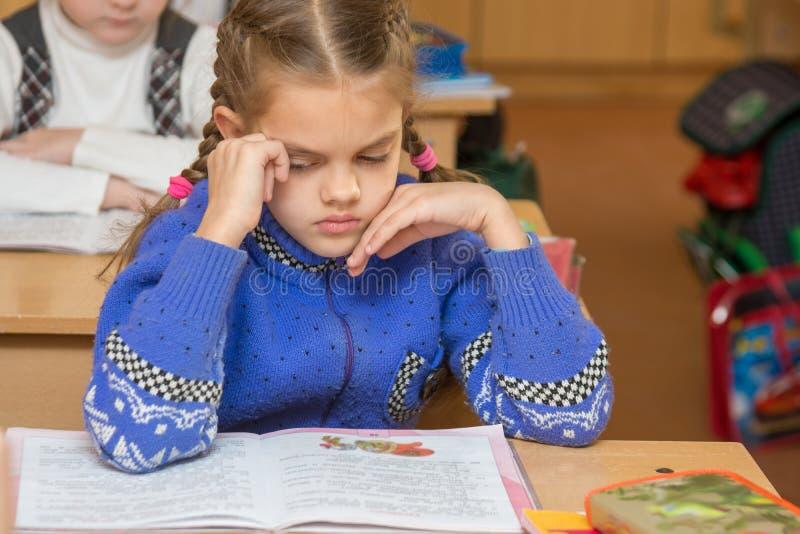 Erstes Sortierermädchen fühlt sich im Klassenzimmer in der Schule schlecht stockbild