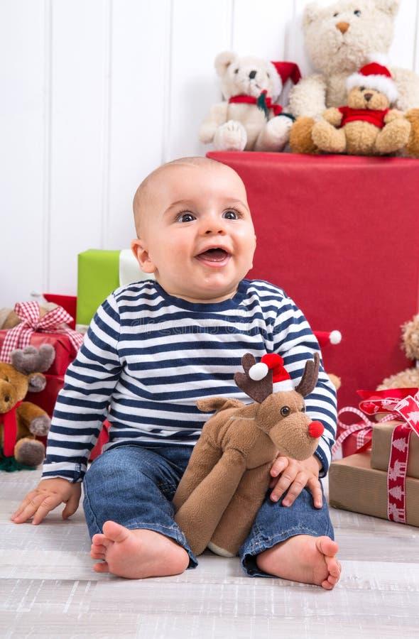 Erstes Weihnachten: barfüßigbaby mit Elchen unter Geschenken und c lizenzfreie stockfotos