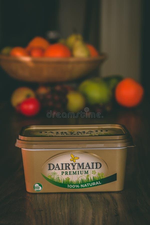 Erstklassiger Behälter des Milchmädchens Butterauf einen Holztisch mit gesunder Frucht im Hintergrund stockfoto