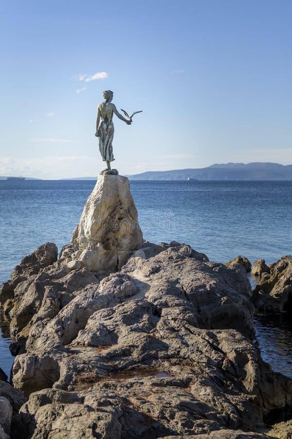 Erstmädchen mit Seemöwe, Statue auf Felsen, Opatija, Kroatien lizenzfreie stockfotos