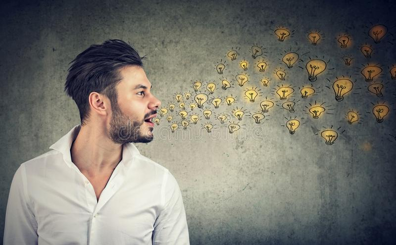 Erudite man talking spreading smart ideas with light bulbs coming out of his mouth royalty free stock photo