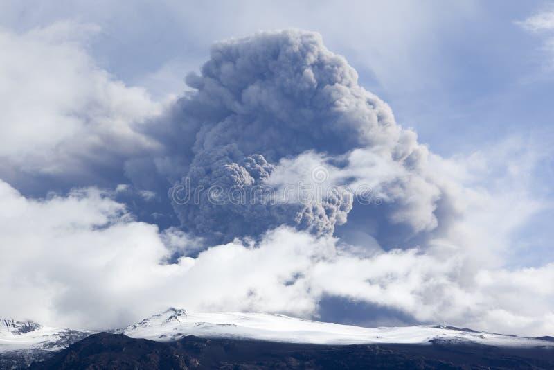 Erupción del volcán en la ceniza de Islandia y el cielo azul imagen de archivo