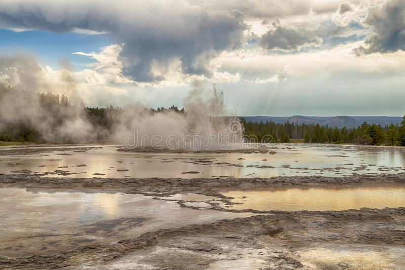 Erupting Great Fountain Geyser in Yellowstone National Park, Wyoming, USA. Beautiful clouds and light rays falling on the geyser, making a colorful dramatic royalty free stock photos