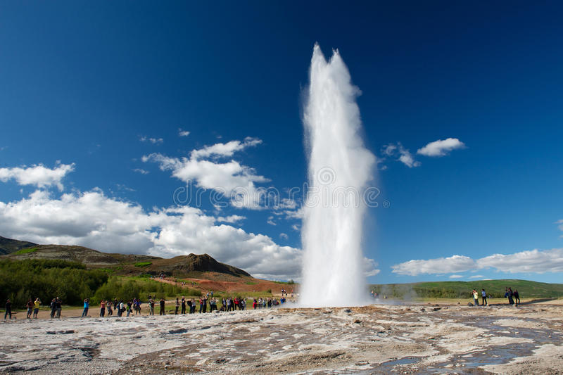 Eruption of Strokkur with tourists waiting around, Golden circle. Impressive eruption of the biggest active geysir, Strokkur, with tourists waiting around stock image