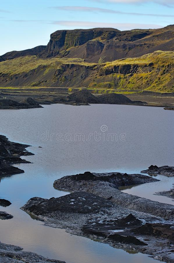 Small pond at Eyjafjalla jokull. Ice covered with ash, Iceland. The 2010 eruptions of Eyjafjallajökull were volcanic events at Eyjafjallajökull in Iceland stock photography