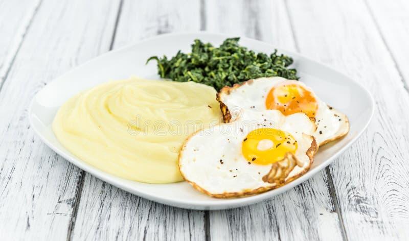 Erva-benta caseiro da batata com ovos fritos e espinafres imagens de stock royalty free