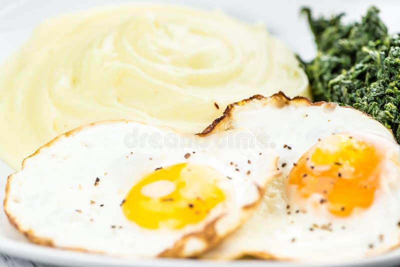 Erva-benta caseiro da batata com ovos fritos e espinafres imagem de stock