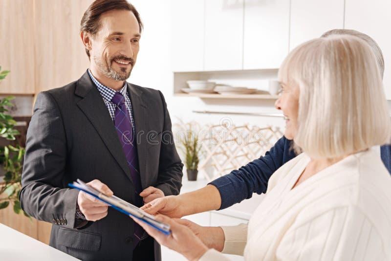 Ervaren advocaat die overleg geven aan bejaard paar over grote aankoop stock afbeelding