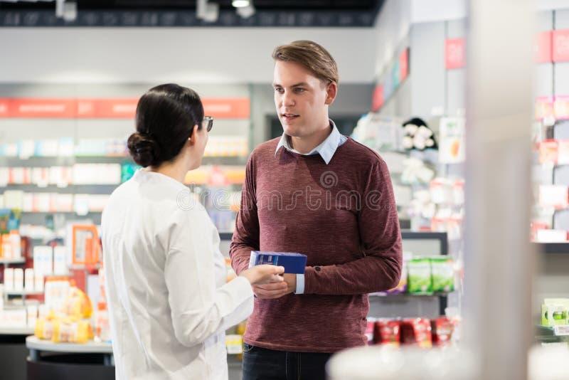 Ervaren apotheker die de aanwijzingen van een geneeskunde controleren stock foto
