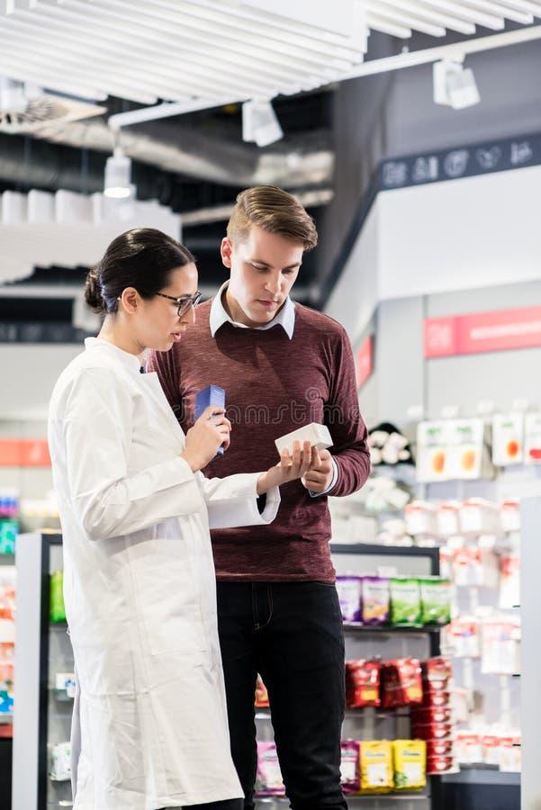 Ervaren apotheker die de aanwijzingen van een geneeskunde controleren stock afbeeldingen