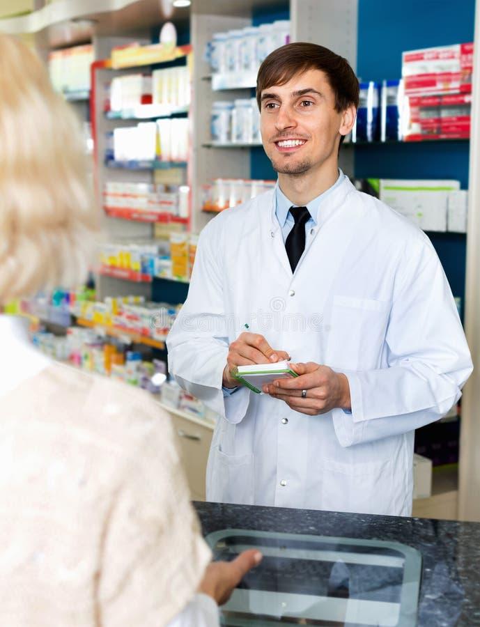 Ervaren apotheker die vrouwelijke klant in farmacy adviseren stock foto