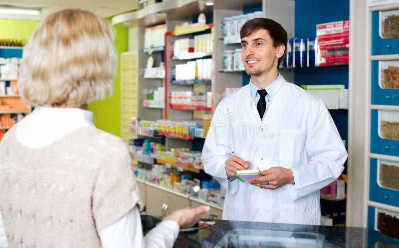Ervaren apotheker die vrouwelijke klant in farmacy adviseren stock afbeeldingen