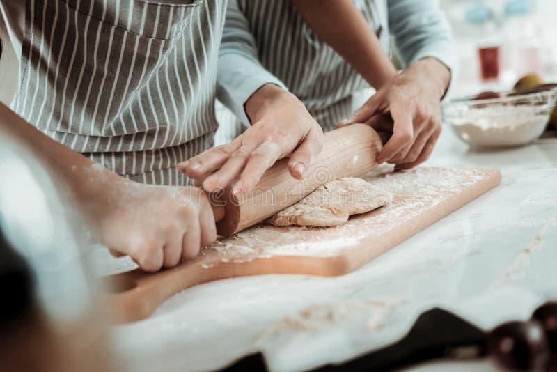 Ervaren dame die aan een kind aan kok helpen stock afbeeldingen