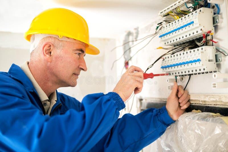 Ervaren elektricien die het elektrowerk doen stock fotografie