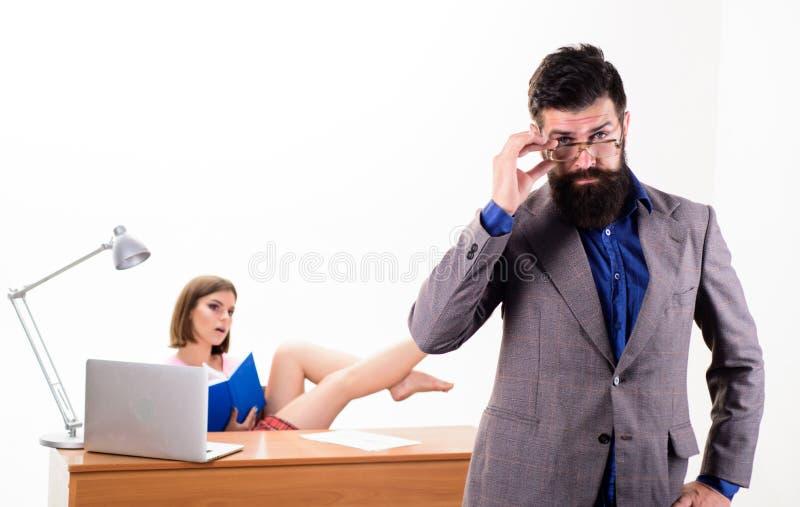 Ervaren en bekwaam Uitvoerende bus die zijn glazen bevestigen terwijl sexy vrouw die op achtergrond werken Bedrijfsbus met stock foto