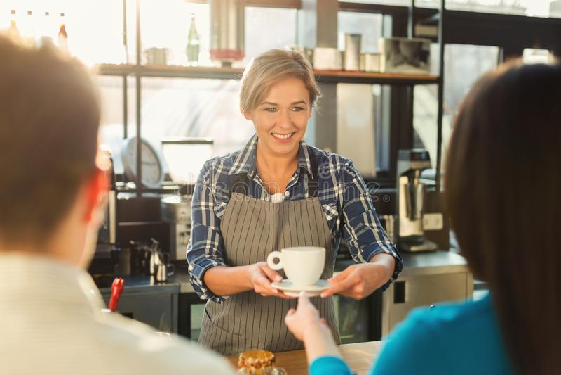 Ervaren het glimlachen barista die tot koffie maken aan klanten stock foto