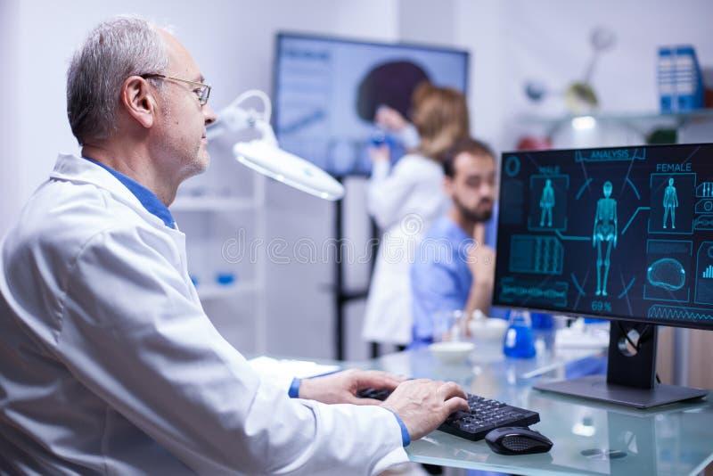 Ervaren hogere wetenschapper die de gegevens in computer van laatste experiment op menselijk lichaam typen stock fotografie