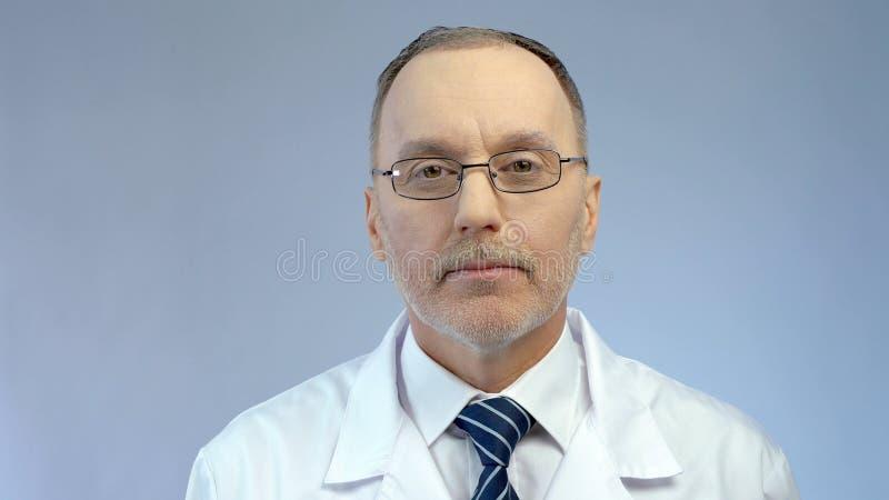 Ervaren kijk van ernstige mannelijke arts, professionele medische hulp bij kliniek royalty-vrije stock afbeelding