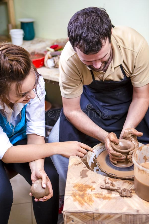 Ervaren Mannelijke Pottenbakkersprivé-leraar Working met Vrouwelijke Leerling met Clay Lump op het Wiel van de Pottenbakker in Wo stock afbeelding