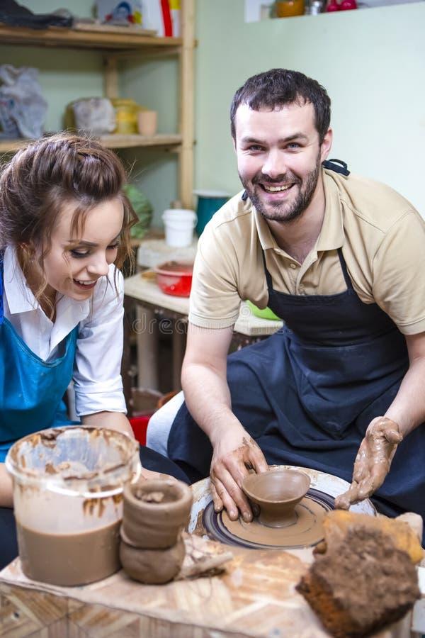 Ervaren Mannelijke Pottenbakkersprivé-leraar Working met Vrouwelijke Leerling met Clay Lump op het Wiel van de Pottenbakker in Wo stock foto