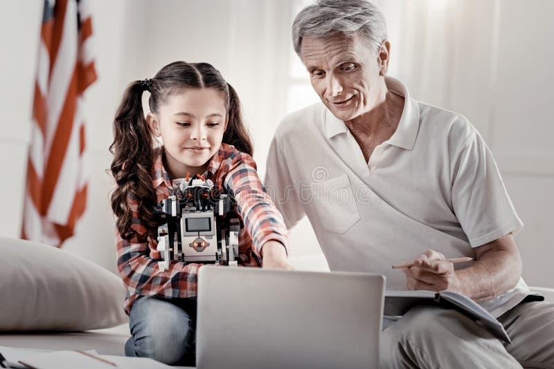 Ervaren opa die nieuwsgierige kleindochterwiskunde verklaren royalty-vrije stock afbeeldingen