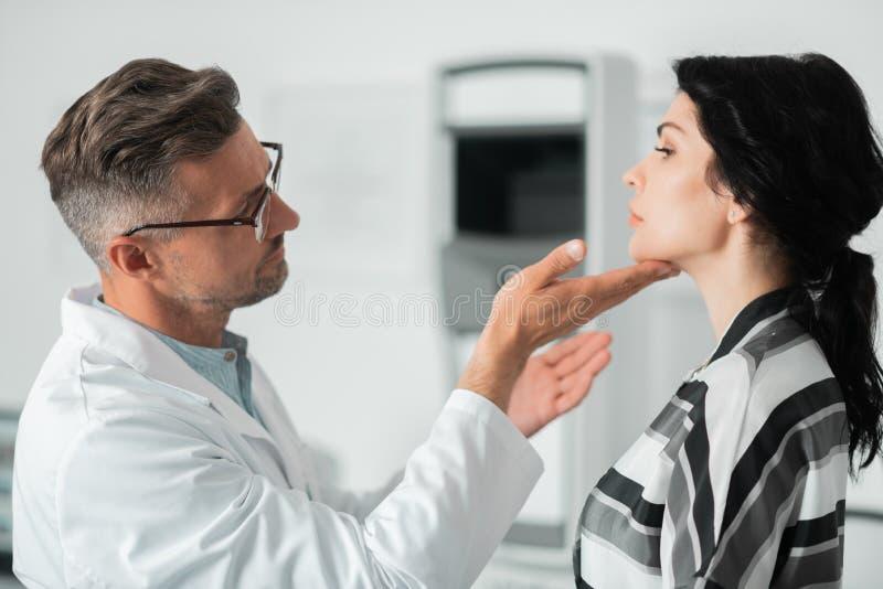 Ervaren schoonheidsmiddelenchirurg die gezicht van mooie vrouw onderzoeken royalty-vrije stock foto
