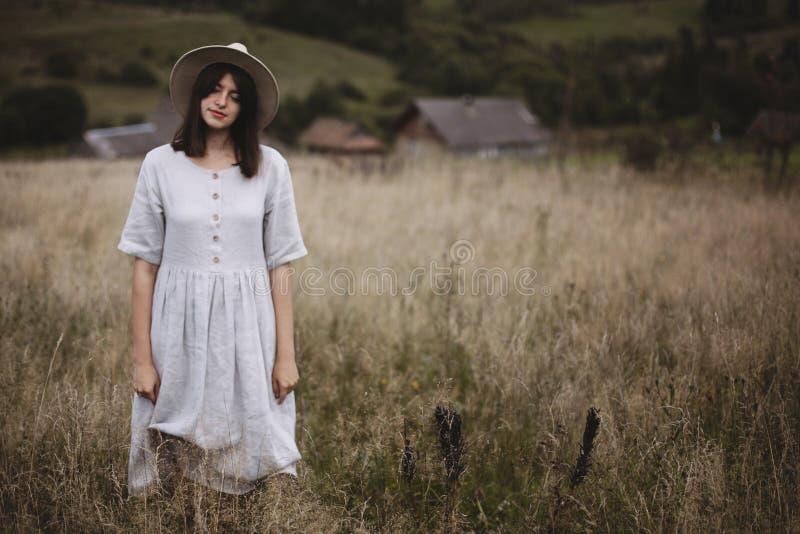 Ervas e wildflowers na imagem borrada do campo da menina à moda no levantamento de linho do vestido e do chapéu Mulher de Boho qu imagem de stock