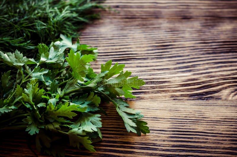Ervas verdes frescas do aneto e da salsa na tabela de madeira rústica Vista superior com espaço da cópia imagem de stock