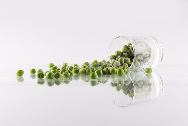 Ervilhas verdes em um vidro foto de stock