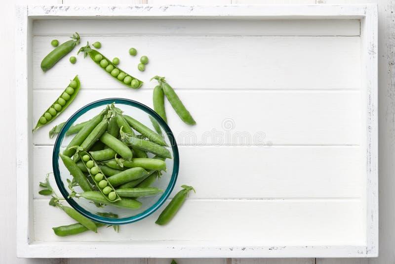 Ervilhas verdes frescas na bandeja de madeira branca imagens de stock