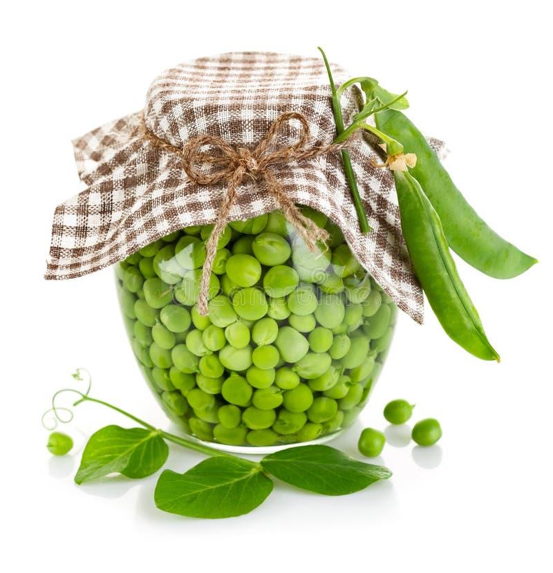 Ervilhas verdes no frasco de vidro imagem de stock
