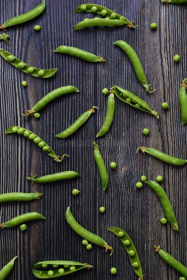 Ervilhas verticais no teste padrão das vagens Opinião superior o legume fresco em uma vagem de ervilha verde de madeira escura do imagens de stock
