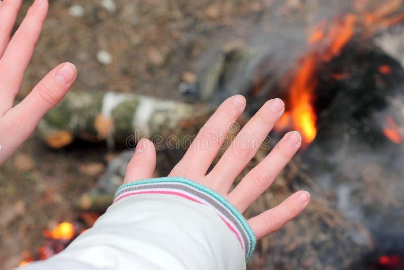 Erwärmung seiner Hände nahe dem Feuer stockfotos