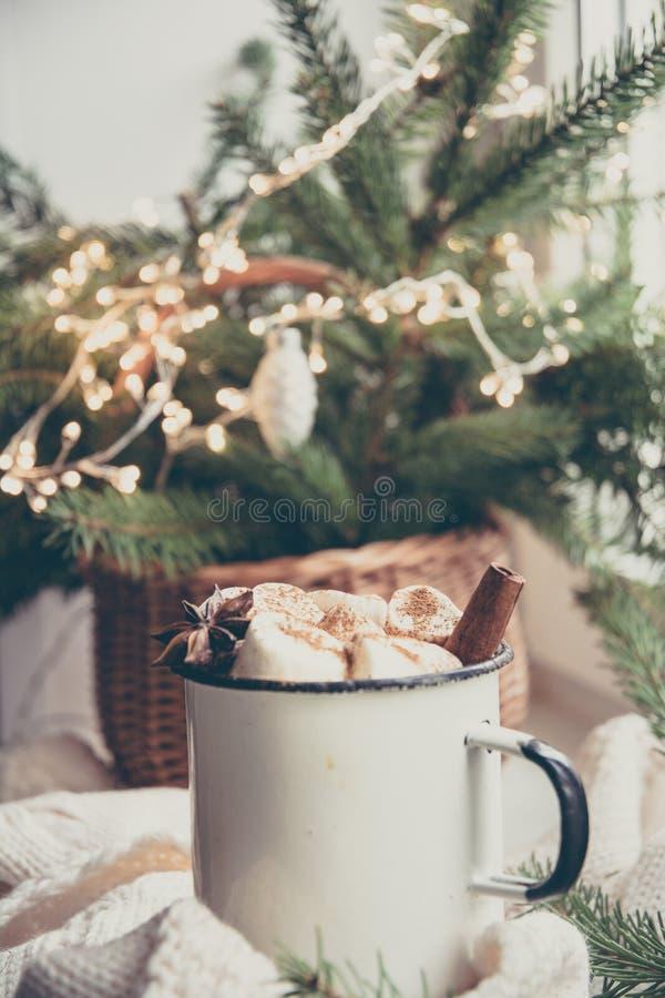 Erwärmungsbecher des Winters Schokolade mit Eibisch auf Fensterbrett mit Weihnachtsbaumdekor lizenzfreie stockfotos