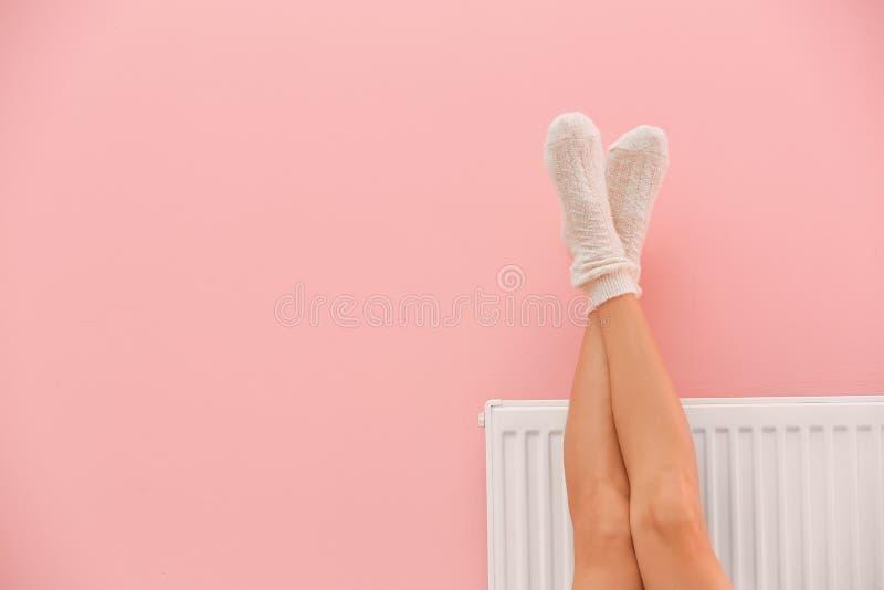 Erwärmungsbeine der Frau auf Heizungsheizkörper nahe Farbwand stockfotos