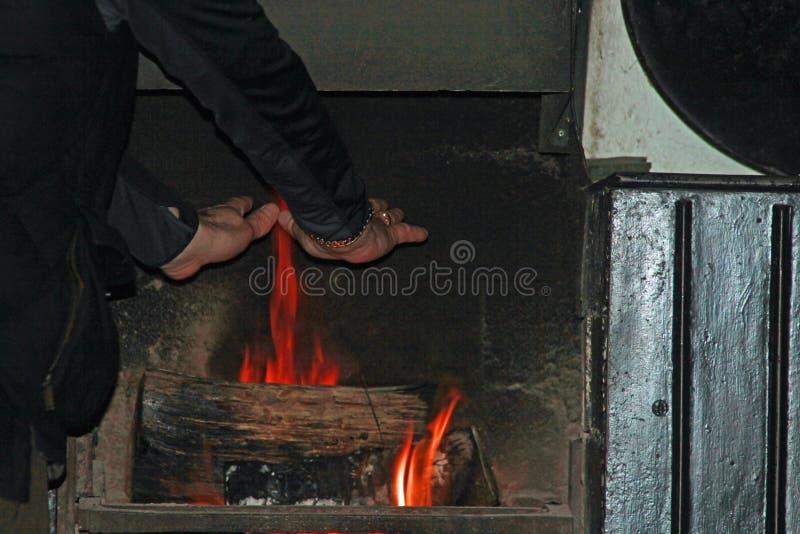 Erwärmungshände auf einem Holzfeuer stockfotos