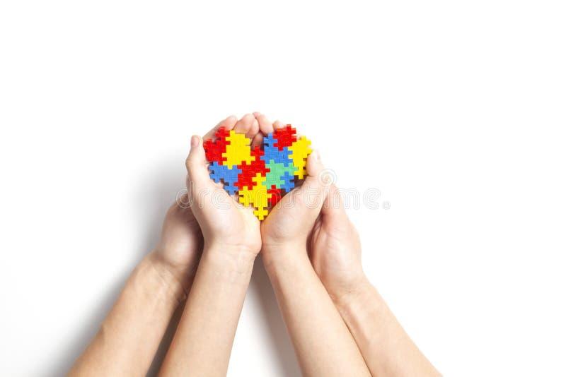 Erwachsen- und Kinderhände, die buntes Herz auf weißem Hintergrund halten stockbilder