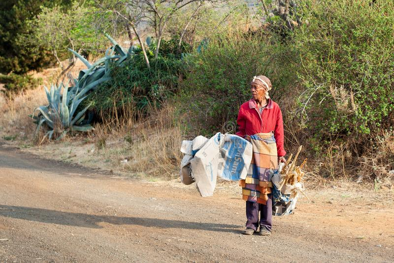 Erwachsene afrikanische Frau im nationalen umfassenden Kleid auf Dorfstraße trägt Abfall und Brennholz, alte Basothofrau entlang  lizenzfreies stockfoto