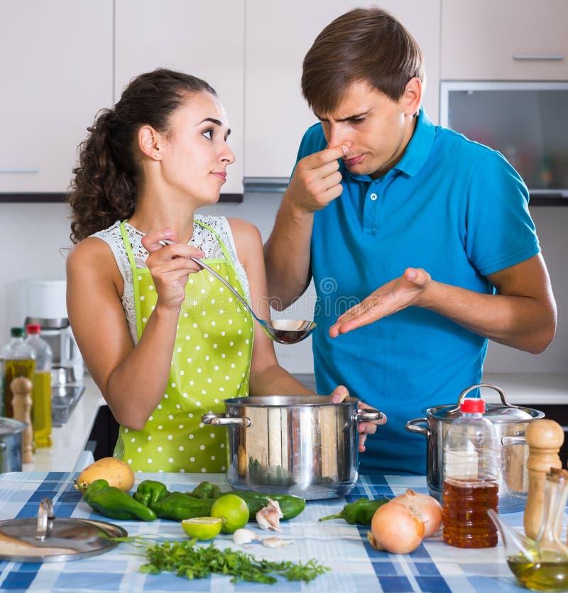 Erwachsene, die widerlichem Geruch des Lebensmittels von der Kasserolle glauben lizenzfreies stockbild