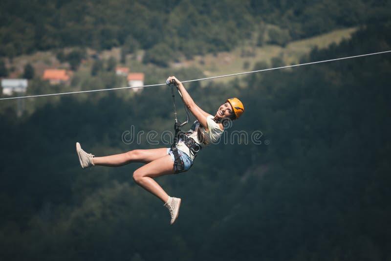 Erwachsene Frau auf Ziplinie stockfoto