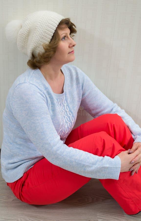 Erwachsene Frau in der Kappe und in Strickjacke, die nahe der Wand sitzen lizenzfreie stockfotos