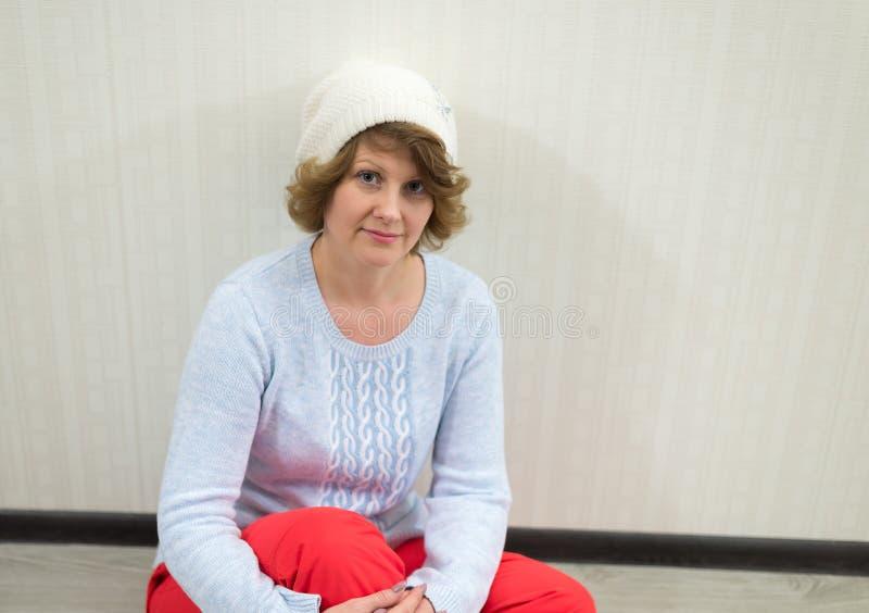 Erwachsene Frau in der Kappe und in Strickjacke, die nahe der Wand sitzen stockfoto