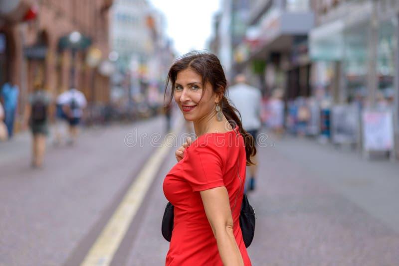 Erwachsene Frau, die über Schulter Kamera betrachtet lizenzfreies stockbild