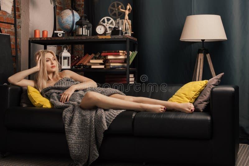 Erwachsene Frau, die auf der Couch in einer woolen Decke im Innenraum liegt stockfotos