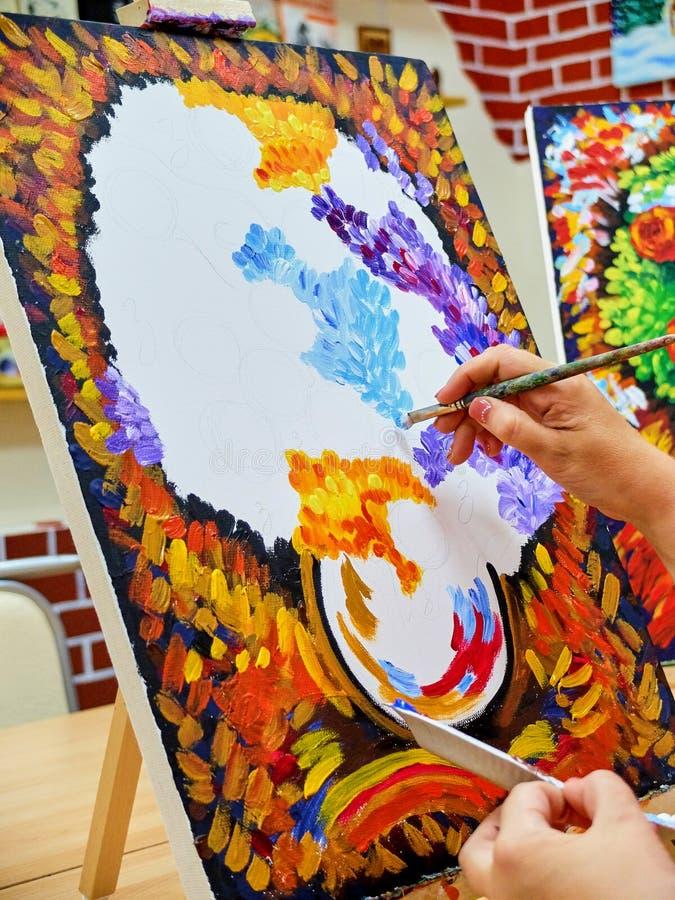 Erwachsene Frau, die colrful Blumenblumenstrauß auf dem großen Segeltuch zeichnet lizenzfreies stockfoto