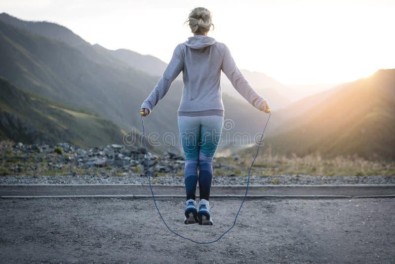 Erwachsene Frau, die draußen früh morgens trainiert Oben springen stockbild