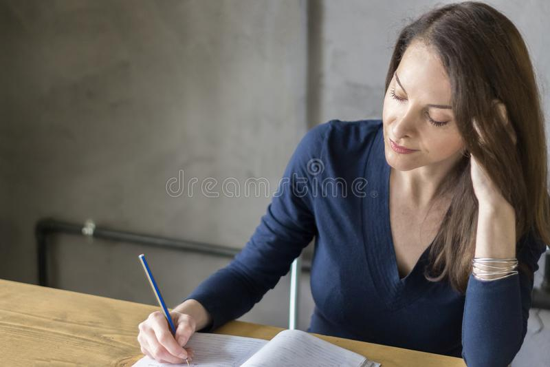 Erwachsene Frau, die Schreiben auf einem Notizbuch konzentriert studiert stockbilder
