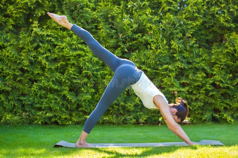 Erwachsene Frau, die Yoga im sonnigen Morgenpark tut lizenzfreie stockfotos
